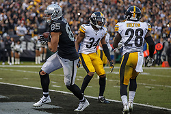 OAKLAND, CA - DECEMBER 09: Tight end Derek Carrier #85 of the Oakland Raiders scores a touchdown past safety Terrell Edmunds #34 of the Pittsburgh Steelers and cornerback Mike Hilton #28 during the fourth quarter at O.co Coliseum on December 9, 2018 in Oakland, California. The Oakland Raiders defeated the Pittsburgh Steelers 24-21. (Photo by Jason O. Watson/Getty Images) *** Local Caption *** Derek Carrier; Terrell Edmunds; Mike Hilton