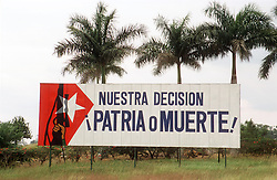 Patriotic revolutionary street hoarding or poster in Cuba saying 'Country or Death' and featuring a picture of a machine gun held aloft,