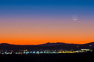 """The 24-hour-old waxing crescent Moon north of Venus (at left), now emerging into the evening sky as a prominent """"evening star."""" Taken at 6 pm MST, Monday, December 22, 2014, the day after winter solstice, from just east of SIlver City, New Mexico, the lights below. Earthshine is visible on the dark side of the Moon. .Taken with the 135mm lens and Canon 60Da."""
