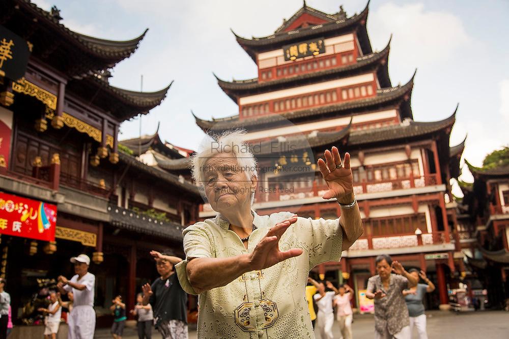 Elderly women practice Tai Chi in Yu Yuan Gardens bazaar Shanghai, China