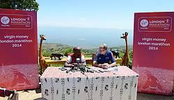 © London News Pictures. 30/01/2013. Iten, Kenya. VIRGIN MONEY LONDON MARATHON 2014 PREVIEW... Mo Farah (left), GB is asked questions by London Marathon race director Hugh Brasher (right), and members of the press about his upcoming marathon debut. The backdrop is The Kerio Valley, which forms part of The Rift Valley. Photo credit: Mike King/London Marathon/LNP