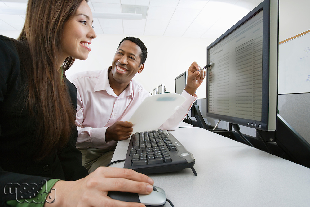 Man and woman using computer together