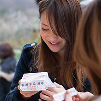 "Voyagers traveled on the ""Kyoto Culture and Sweets"" field program to the Kinkakuji Temple, Nijo Castle, and Kiyomizu (Pure Water) Temple before learning how to make traditional Japanese sweets. A Japanese girl reads her fortune on a slip of paper at Jishu-jinga, a separate shrine located above Kiyomizu-dera's main hall."