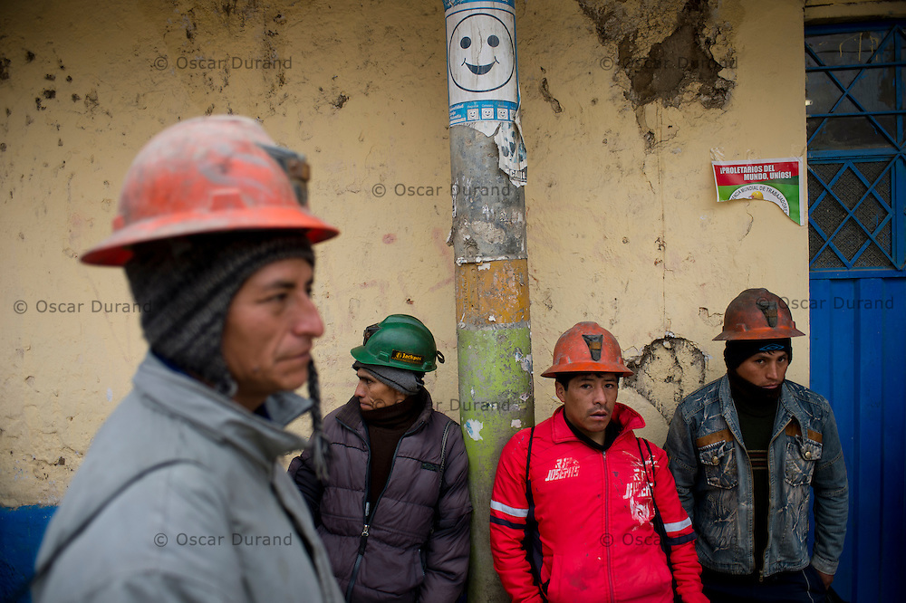 Miners wait for the bus that will take them to work to one of the area mines.