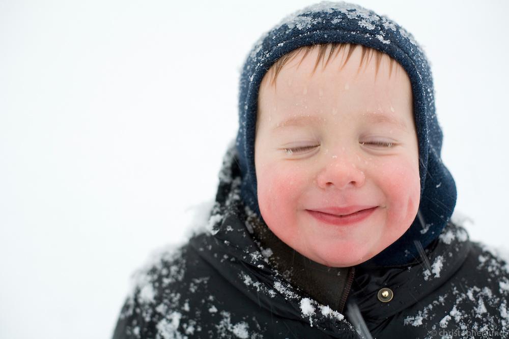 A small boy having fun in the wintersnow. Snow on hat and clothes...Ari Carl að leika sér úti í snjónum.