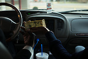 "MONTGOMERY, AL – JANUARY 25, 2016: Cabbie Michael Harris takes money from a customer at a fast food drive through. In 2011, the downtown Montgomery Greyhound bus station was converted into a museum to honor the freedom riders, who endured a violent attack there in 1961. The replacement bus station, located four miles from downtown, is a prime business opportunity for independent cabbies like Michael Harris, who make a living serving passengers unwilling to rely on city buses. Many characterize the public bus system in Montgomery as unsafe and unreliable, so wary passengers cough up $2 per mile for trips in Mr. Harris' 2005 Lincoln Navigator, traveling across town for fast food, or sometimes as far as New York City. ""This is my life,"" Harris said. ""I love driving, and I help people out. It's just in my heart."""