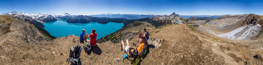 From stunning Panorama Ridge, admire the vibrant turquoise color of Garibaldi Lake. At left rises Mount Garibaldi above Garibaldi Lake. At right are the Black Tusk and Helm Glacier. Garibaldi Provincial Park is east of the Sea to Sky Highway (Route 99) between Squamish and Whistler in the Coast Range, British Columbia, Canada. A hiking loop to Garibaldi Lake via Taylor Meadows Campground is 11 miles (18k) round trip, with 3010 ft (850m) gain. Panorama Ridge is 6 miles (10k) RT with 2066 ft (630m) gain from either Taylor Meadows or Garibaldi Lake Campground (or 17 miles RT with 5100 ft gain from Rubble Creek parking lot). Global warming/climate change: The Helm Glacier had an area of 4.3 square kilometers in 1928, but declined by 78% to 0.92 square kilometers as of 2009. The Helm Glacier's melting trend mirrors that of all glaciers in the Pacific Northwest and fits into the pattern of glacier retreat across Canada (measured in the Canadian Glacier Retreat Index). From the early 1700s to 2005, half (51%) of the glacial ice cover of Garibaldi Provincial Park melted away (reference: Koch et al. 2008, web.unbc.ca). The record of 1900s glacier fluctuations in Garibaldi Park is similar to that in southern Europe, South America, and New Zealand, suggesting a common, global climatic cause. This panorama was stitched from 28 overlapping images.