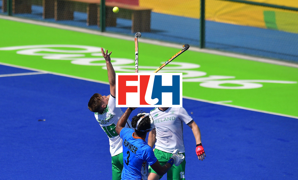 Ireland's Shane O'donoghue (L) and India's Rupinder Pal Singh (C) fight for the ball as Ireland's Eugene Magee looks on during the men's field hockey India vs Ireland match of the Rio 2016 Olympics Games at the Olympic Hockey Centre in Rio de Janeiro on August, 6 2016. / AFP / Carl DE SOUZA        (Photo credit should read CARL DE SOUZA/AFP/Getty Images)