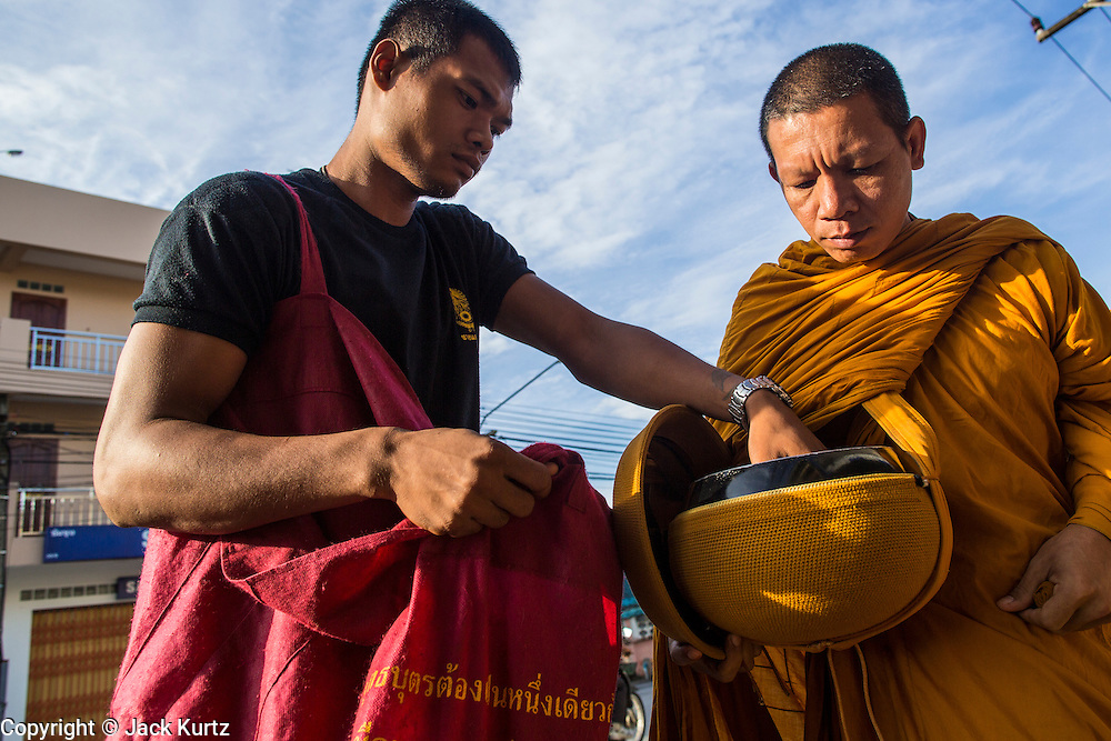 25 OCTOBER 2012 - PATTANI, PATTANI, THAILAND:  Buddhist monks on morning alms rounds with plainsclothes security personnel in Pattani, Thailand. More than 5,000 people have been killed and over 9,000 hurt in more than 11,000 incidents, or about 3.5 a day, in Thailand's three southernmost provinces and four districts of Songkhla since the insurgent violence erupted in January 2004, according to Deep South Watch, an independent research organization that monitors violence in Thailand's deep south region that borders Malaysia.    PHOTO BY JACK KURTZ