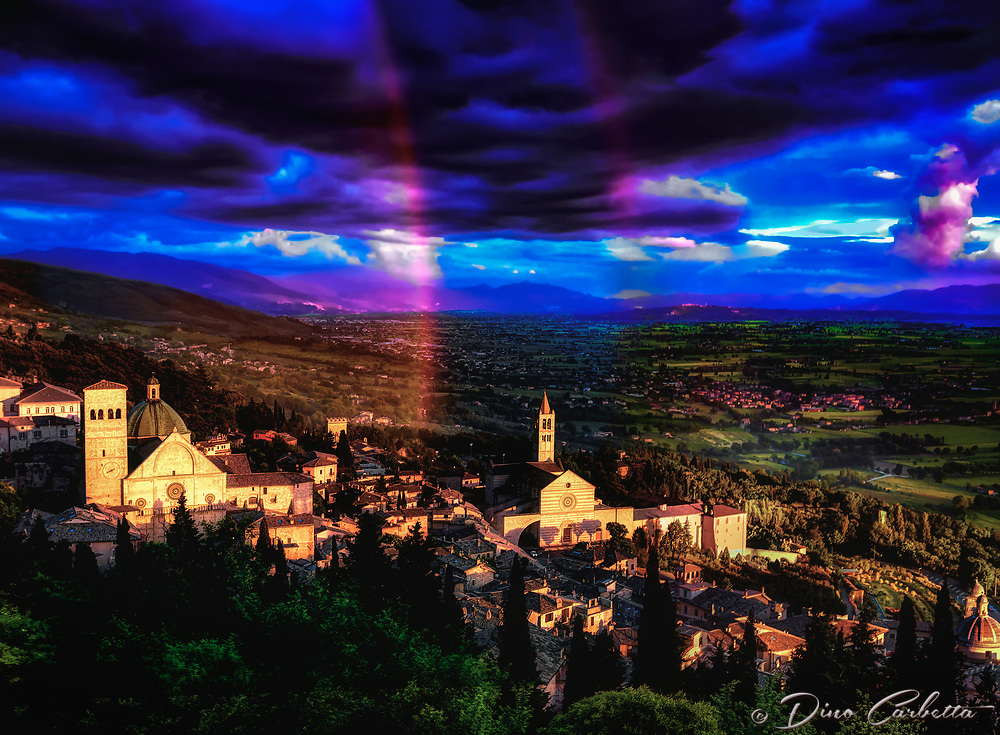 """""""Double rainbow of God shines Between San Rufino and St. Clare of Assisi""""...<br /> <br /> This image is perhaps the most blessed and miraculous of my Italian journey.  Upon arrival early that day in Assisi, I began taking photos the second I parked at Hotel Giotto just inside the walls in the foothills of Assisi. Perhaps Saint Francis arranged the dramatically perfect skies and coordinated every encounter. Beginning at the Basilica of Saint Francis, every second of the climb to the top of the mountain to the fortress Rocca Maggiore, a new surprise awaited around every corner.  Upon my final steps to the top at almost sunset, the clouds parted and the low sun brightened as a slight mist of rain came down.  Looking back over my shoulder, I was mesmerized at the appearance of a double rainbow from the heavens shining down between the Duomo of Saint Rufino, and the Basilica of Saint Clare. I was able to take a few horizontal and vertical images of the great length and depth of the rainbow just before the sun dropped down below the horizon...and, it slowly faded.  My Italian journey was now and forever blessed by the hand of God."""