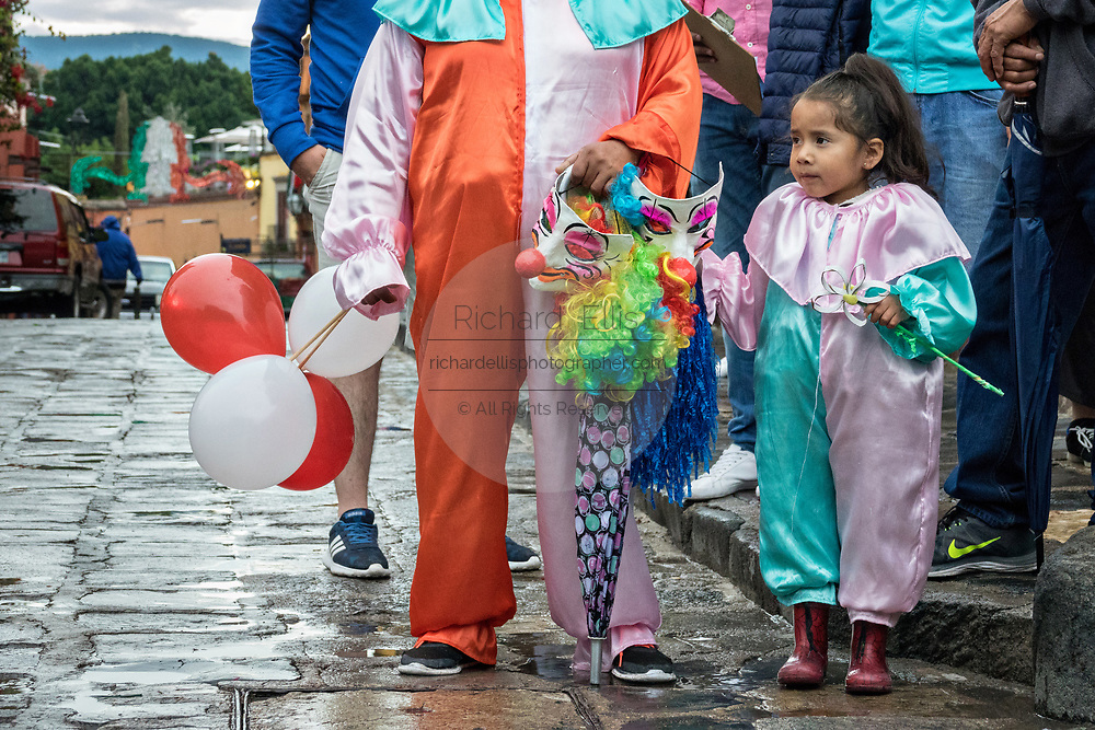 A young girl in clown costume watches a procession pass through the Jardin Allende during the week long fiesta of the patron saint Saint Michael September 24, 2017 in San Miguel de Allende, Mexico.