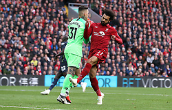 Manchester City goalkeeper Ederson collects the ball as Liverpool's Mohamed Salah reacts during the Premier League match at Anfield, Liverpool.