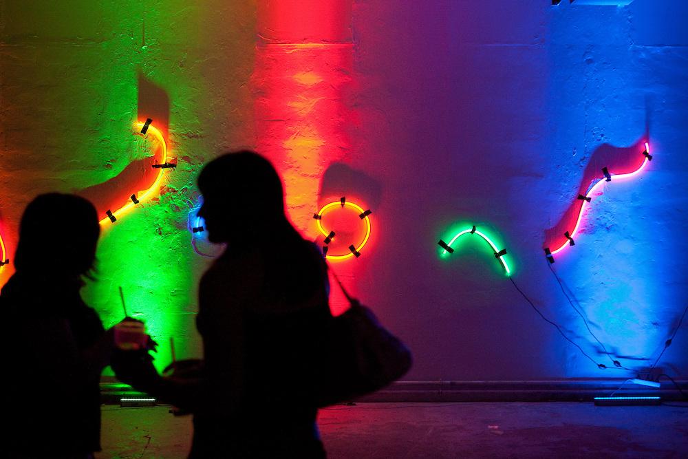 """Besucher der MeetFactory im Prager Stadtteil Smichov während einer Abendveranstaltung mit Kunst und Live Musik. Eine Licht Installation für die nachfolgende """"Chill Out"""" Party."""