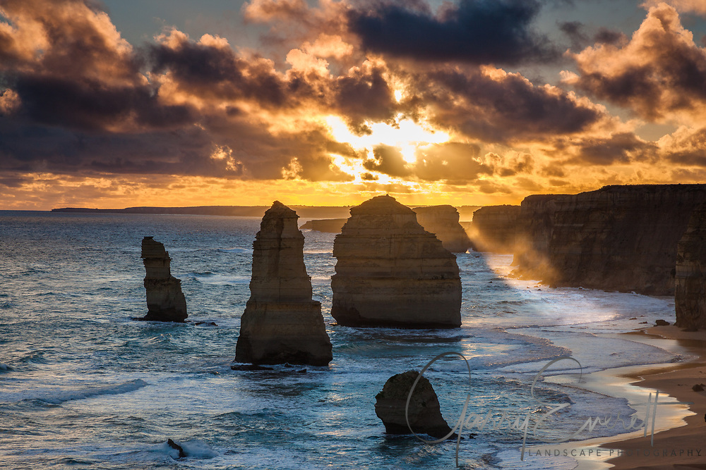 Sunset at the 12 Apostles, sun breaking though the cloud to create a sunbeam