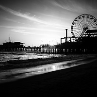 Santa Monica Pier black and white picture. Photo incudes the sun setting over Santa Monica Pier and Ferris Wheel along the Pacific Ocean in Los Angeles County Southern California.