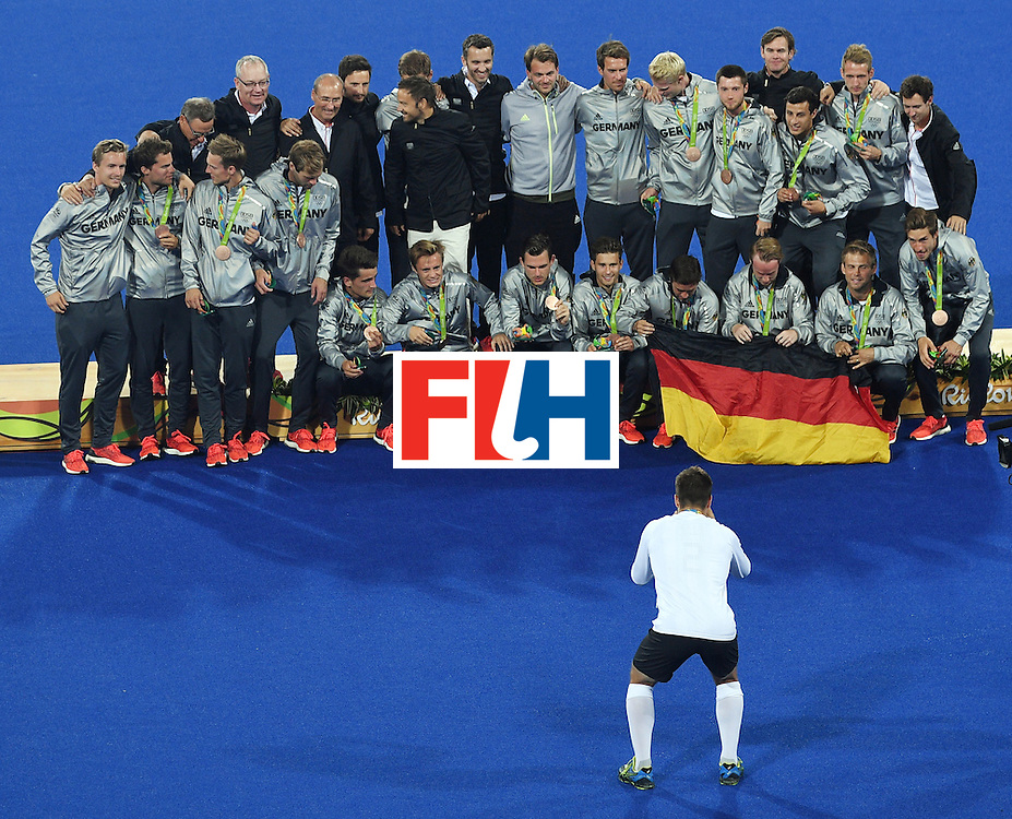 Germany's players celebrate on the podium with their bronze medals during the men's field hockey medals ceremony of the Rio 2016 Olympics Games at the Olympic Hockey Centre in Rio de Janeiro on August 18, 2016. / AFP / MANAN VATSYAYANA        (Photo credit should read MANAN VATSYAYANA/AFP/Getty Images)