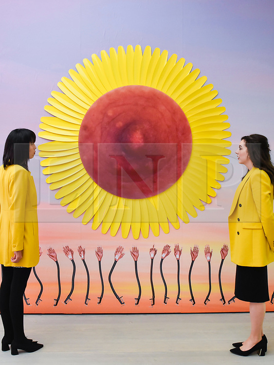 """© Licensed to London News Pictures. 25/09/2019. LONDON, UK. Staff members pose with """"Flower Nipple Colza Yellow"""", 2019, by Sarra Badel at the preview of START, a contemporary art fair comprising eclectic works from a variety of international emerging artists.  The fair takes place at the Saatchi Gallery in Chelsea 26 to 29 September 2019.  Photo credit: Stephen Chung/LNP"""