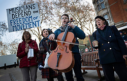 © Licensed to London News Pictures. 11/12/2018. London, UK. A group of musicians sing and play outside Parliament holding a placard in support of freedom of movement. Prime Minister Theresa May is touring European countries today in a bid to obtain changes to the Brexit withdrawal agreement.  Photo credit: Peter Macdiarmid/LNP