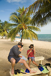 Father and son trying on snorkel gear on beach, Jaguar Reef Lodge, Hopkins, Stann Creek District, Belize, Central America   PR, MR