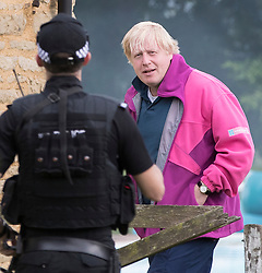 © Licensed to London News Pictures. 10/06/2017. Oxford, UK. Foreign Secretary Boris Johnson is seen at his Oxfordshire home talking to armed police. Theresa May has formed a minority government with the support of the DUP after failing to gain enough seats in the general election. Photo credit: Peter Macdiarmid/LNP