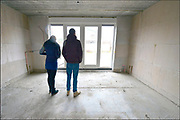 Nederland, Overasselt, 26-7-2016 In dit dorp heeft een aannemer een rijtje huizen gebouwd. De toekomstige bewoners mogen vandaag kijken hoe het ervoor staat. Ook kunnen zij hun voorkeuren aangeven over de verdere afwerking van hun huis. Het zijn goedkope koophuizen gericht op jonge mensen , starters. FOTO: FLIP FRANSSEN