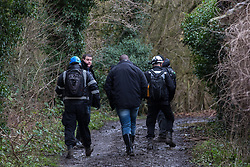 Harefield, UK. 14 January, 2020. Enforcement agents working on behalf of HS2 walk along a public right of way leading to a protection camp from which Stop HS2 activists are being evicted. Part of the nearby Colne Valley protection camp was evicted by bailiffs last week. 108 ancient woodlands are set to be destroyed by the high-speed rail link and further destruction of trees for HS2 in the Harvil Road area is believed to be imminent.