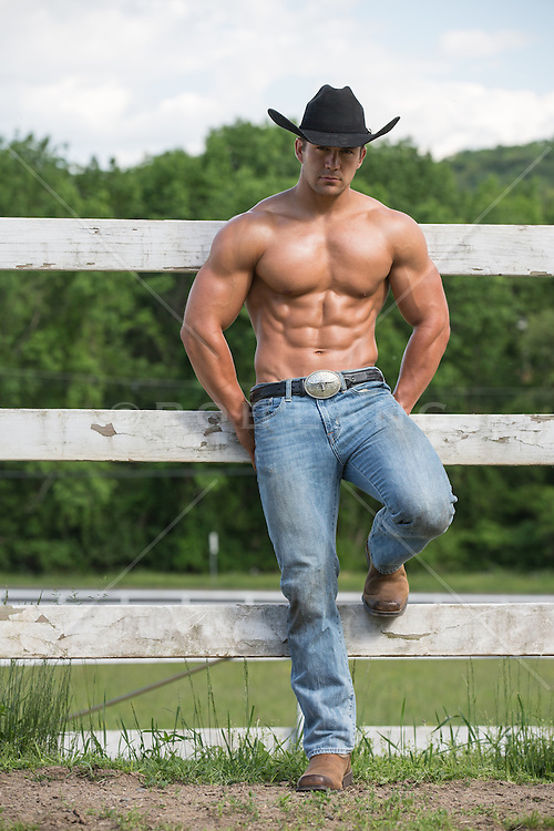 shirtless hunky cowboy leaning on a fence