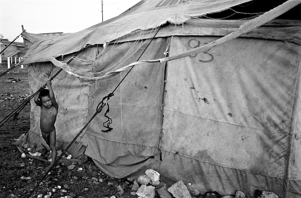 A boy alone in the early morning, plays outsides his families tent. ..Konik camp - a refugee camp for Roma (gypsies) displaced from Kosovo, Montenegro.