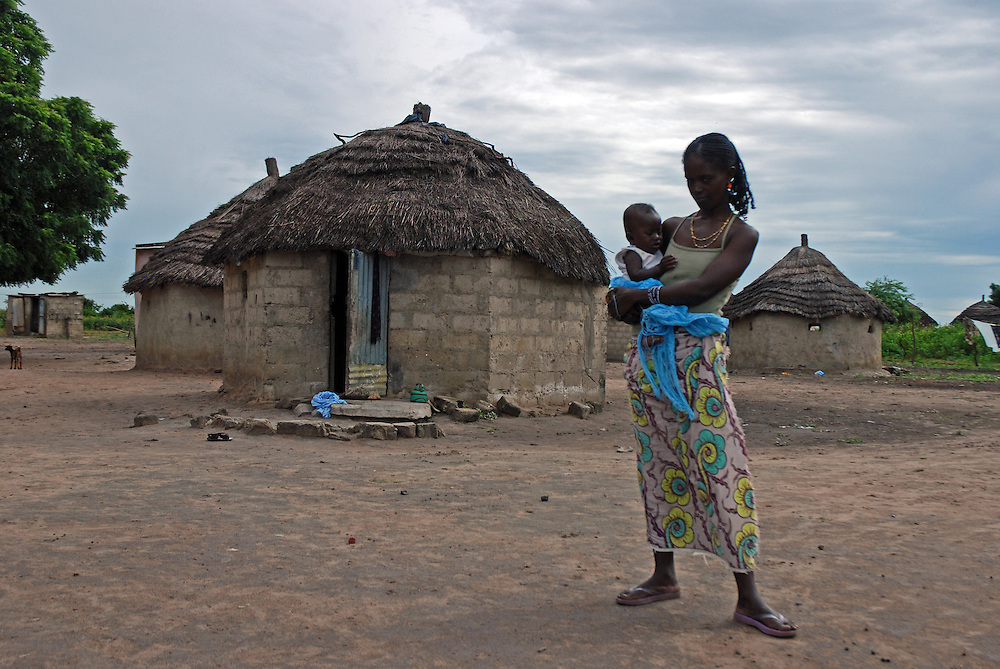A young senegalese mother holds her baby, stands outside her breeze block and thatch construction hut.  This is one of numerous small clusters of huts and shacks growing up around the fishing town of M'bour, Senegal.   M'bour is currently the 5th largest, and one of the fastest growing town in Senegal.  With unemployment high, men arrive to find work in the, largely unregulated fishing industry.  Around the main town small clusters of huts and shacks spring up to house this burgeoning population, most with no facilities whatsoever.  With no waste disposal plastic rubbish piles up along the paths between these settlemets and the main town.