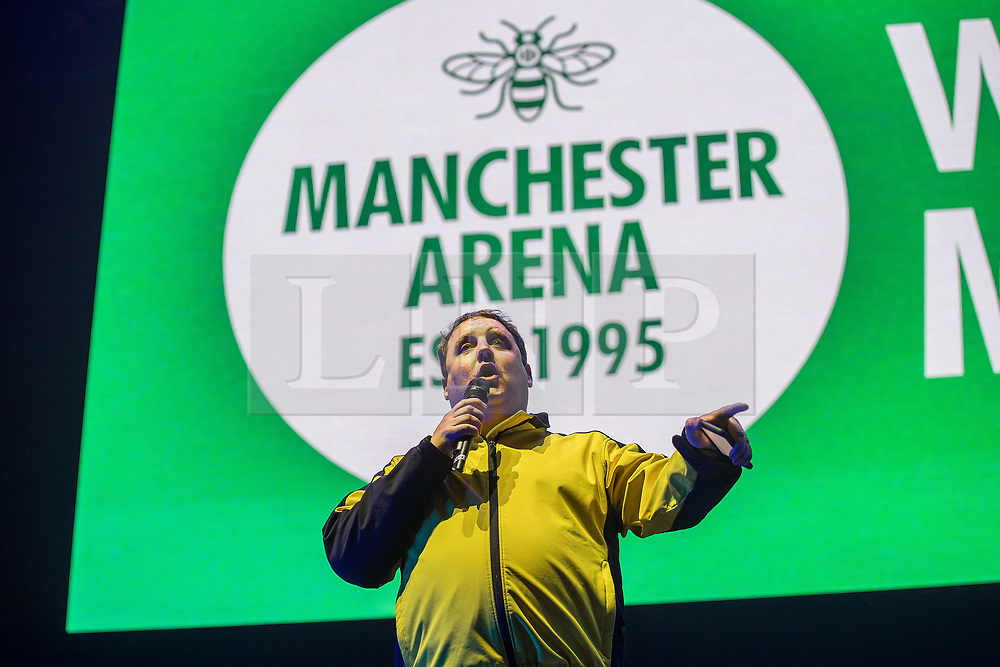 © Licensed to London News Pictures . 09/09/2017. Manchester , UK . PETER KAY on the stage wearing a Showsec security top . We Are Manchester reopening charity concert at the Manchester Arena with performances by Manchester artists including  Noel Gallagher , Courteeners , Blossoms and the poet Tony Walsh . The Arena has been closed since 22nd May 2017 , after Salman Abedi's terrorist attack at an Ariana Grande concert killed 22 and injured 250 . Money raised will go towards the victims of the bombing . Photo credit: Joel Goodman/LNP