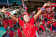 "Apr 4, 2010 - BANGKOK, THAILAND: A man with a Thaksin Shinawatra mask dances in front of the Red Shirts' main stage in Ratchaprasong intersection in Bangkok, Sunday, Apr. 4. Thousands of members of the United Front of Democracy Against Dictatorship (UDD), also known as the ""Red Shirts"" and their supporters moved their anti government protests into central Bangkok Apr. 4 when they occupied Ratchaprasong intersection, the site of Bangkok's fanciest shopping malls and several 5 star hotels. The Red Shirts are demanding the resignation of current Thai Prime Minister Abhisit Vejjajiva and his government. The protest is a continuation of protests the Red Shirts have been holding across Thailand. They support former Prime Minister Thaksin Shinawatra, who was deposed in a coup in 2006 and went into exile rather than go to prison after being convicted on corruption charges. Thaksin is still enormously popular in rural Thailand. This move, away from their traditional protest site in the old part of Bangkok, has gridlocked the center of the city and closed hundreds of stores and restaurants and several religious shrines. There has not been any violence, but the government had demanded that the Red Shirts return to the old part of the city.   PHOTO BY JACK KURTZ"