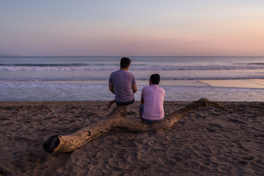 Two men having a conversation on a tree branch at Kayu Putih beach in Canggu.