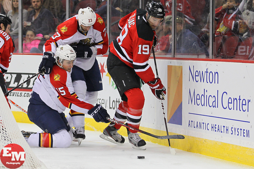Mar 23, 2013; Newark, NJ, USA; New Jersey Devils center Travis Zajac (19) plays the puck while being defended by Florida Panthers center Drew Shore (15) and Florida Panthers defenseman Tyson Strachan (23) during the first period at the Prudential Center.