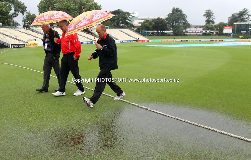 Umpires Evan Gray and Barry Frost inspect the water laden field as rain continues to delay the start of the match. New Zealand White Ferns v Australia, Rose Bowl series. Twenty 20 Cricket match at Seddon Park, Tuesday 28 December 2010. Photo: Andrew Cornaga/photosport.co.nz