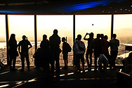 A group taking photos of the sun setting, from the Eureka Skydeck viewing platform in Melbourne, Australia