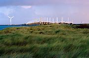 Pijlers van de Oosterscheldekering steken boven de duinen uit. Zeeland provincie.