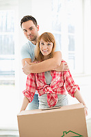 Portrait of man embracing woman in new house
