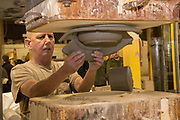 Employee Larry Pipton operates a ram press at Burley Clay in Roseville. Photo by Ben Siegel