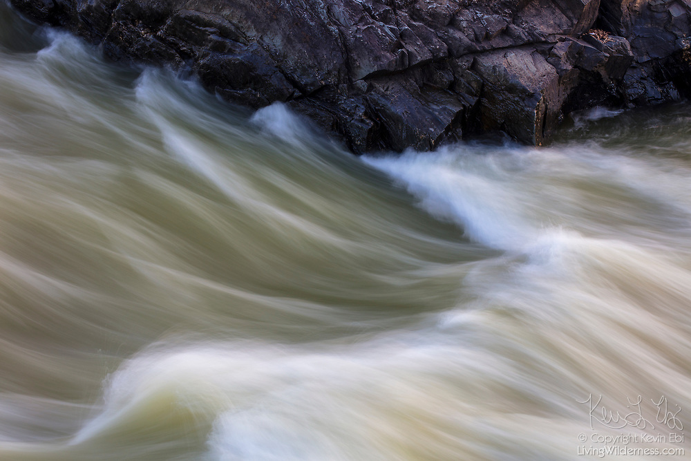 The Potomac River forms a number of small cascades as it runs against a large gorge wall in Great Falls Park, Maryland.