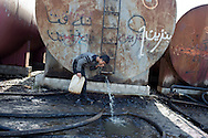 05/02/15 --TANJERO, IRAQ: Jamal (17) smells petrol coming out of a container to test it for its water content.<br /> <br /> Jamal, a Yezidi boy from Sinjar, lives with his displaced family next to an oil refinery in the Kurdish Region of Iraq. He and his cousins run the refinery 24 hours a day with little to no safety equipment. Reporting for this article was supported by a grant from the Pulitzer Center on Crisis Reporting