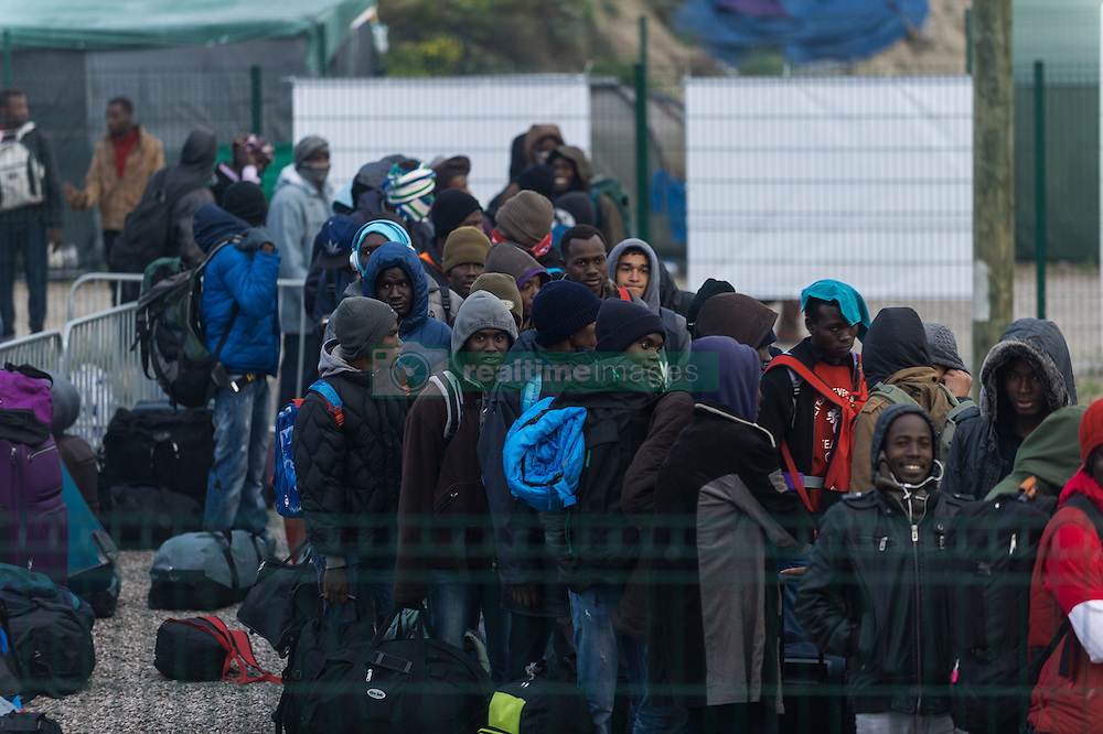 October 24, 2016 - Calais, France - Migrants stand in the official part of the Calais Jungle in a line to leave the camp. The refugee camp on the coast to the English Channel is to be cleared today. The approximately 8,000 refugees are distributed after the registration by busses to various reception centers in France. (Credit Image: © Markus Heine/NurPhoto via ZUMA Press)