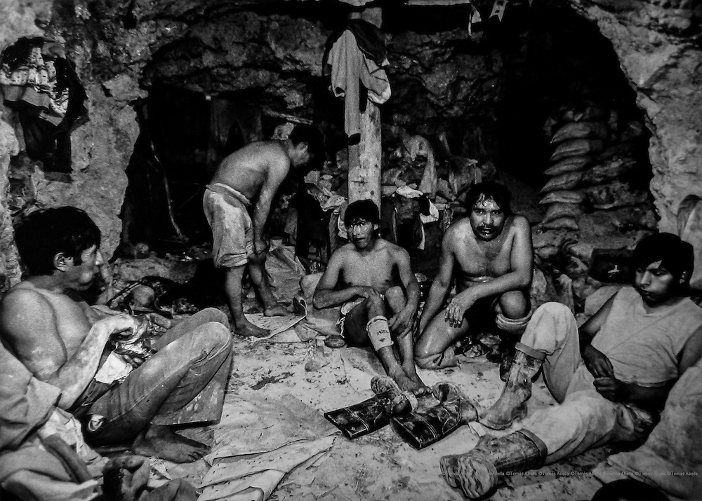 """Working at 4500 metres of altitude and in extreme temperatures means that the """"mandingas"""" have to """"pijchear""""-chew coca leaves- for an hour in a small gallery before going into the mine shaft. Siglo XX tin mine. Llallagua, Bolivia."""