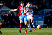 Scunthorpe United defender Cameron Burgess (21) stoops Doncaster Rovers forward John Marquis (9)  during the EFL Sky Bet League 1 match between Scunthorpe United and Doncaster Rovers at Glanford Park, Scunthorpe, England on 23 February 2019.