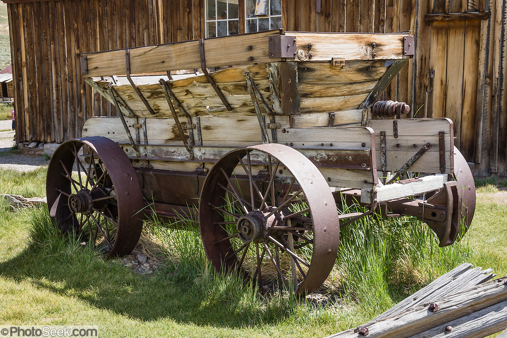 "An historic ore wagon decays outside of the Miner's Union Hall, at the corner of Green Street and Main Street in Bodie, California's official state gold rush ghost town. Bodie State Historic Park lies in the Bodie Hills east of the Sierra Nevada mountain range in Mono County, near Bridgeport, California, USA. After W. S. Bodey's original gold discovery in 1859, profitable gold ore discoveries in 1876 and 1878 transformed ""Bodie"" from an isolated mining camp to a Wild West boomtown. By 1879, Bodie had a population of 5000-7000 people with 2000 buildings. At its peak, 65 saloons lined Main Street, which was a mile long. Bodie declined rapidly 1912-1917 and the last mine closed in 1942. Bodie became a National Historic Landmark in 1961 and Bodie State Historic Park in 1962."