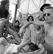 Dom and Jay sitting under a tent next to a van while talking to a group of people at Glastonbury, 1989.
