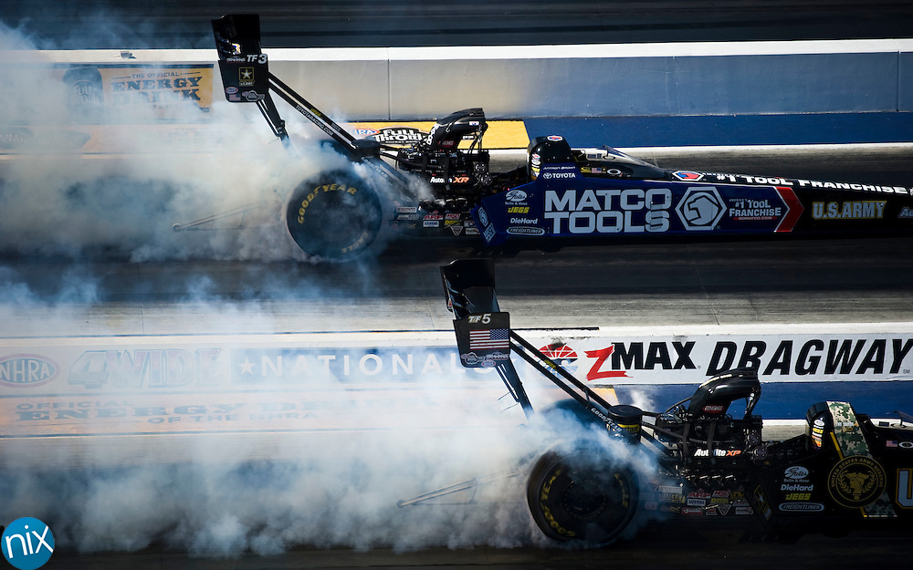 Top Fuel driver Antron Brown, top and Tony Schumacher do burn outs prior to their final qualifying pass during the NHRA 4-Wide Nationals Saturday at zMAX Dragway in Concord.   (photo by James Nix)