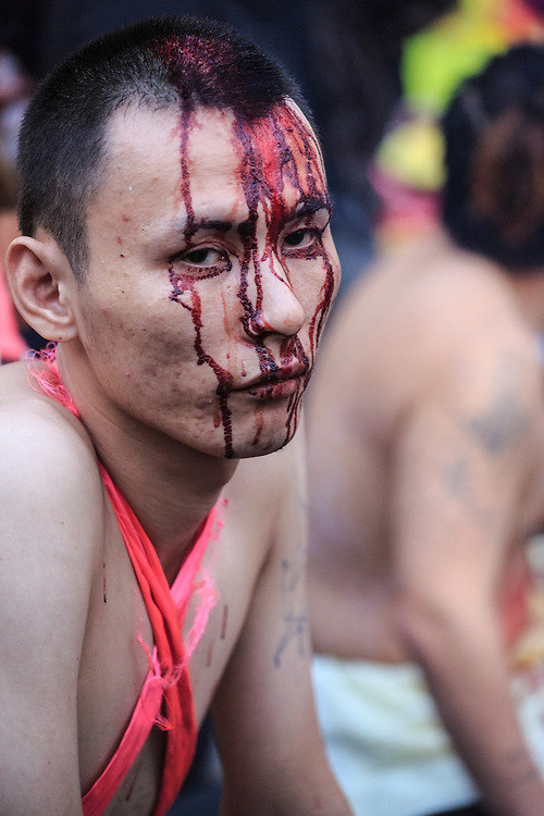 Blood covers the face of a ji tong or spirit medium. The medium becomes possessed by God and beats himself with spiked clubs, swords and similar devices.