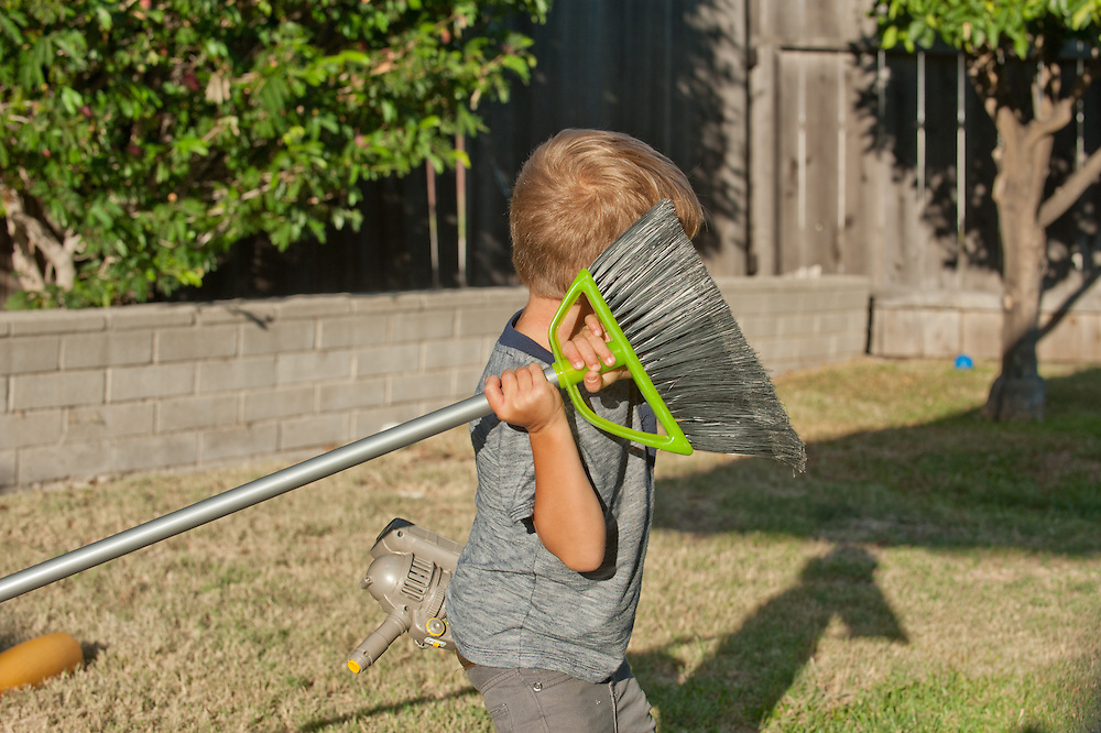 young boy with watergun in back pocket and swinging his broom as make-believe light saber inhis backyard