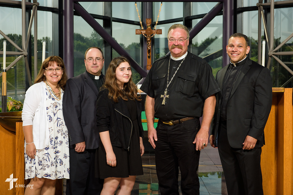 The Rev. Dr. Matthew C. Harrison, president of The Lutheran Church–Missouri Synod, joins new national missionaries, the Rev. Micah Glenn (right), and the Rev. Antonio Lopez with his wife Rebecca and daughter Emilia, at the International Center of The Lutheran Church–Missouri Synod on Monday, June 13, 2016, in Kirkwood, Mo. LCMS Communications/Erik M. Lunsford