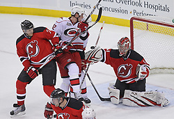 Feb 16; Newark, NJ, USA; New Jersey Devils goalie Johan Hedberg (1) makes a blocker save while New Jersey Devils defenseman Henrik Tallinder (7) defends on Carolina Hurricanes center Eric Staal (12) during the third period at the Prudential Center. The Devils defeated the Hurricanes 3-2.